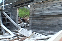Collapsed buildings and rusted equipment lie abandoned in a mountainous area. Stock Footage