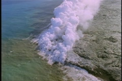 Steam rises as lava flows into the sea in Hawaii. Stock Footage
