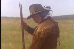 A mountain man dressed in buckskin, aims his rifle. Stock Footage