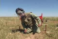 A land mine removal expert prepares to remove a land mine in Iraq. - stock footage