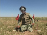 Stock Video Footage of A land mine removal expert prepares to remove a land mine in Iraq.
