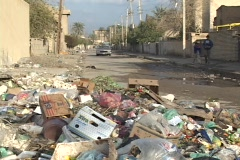 Cars and Iraqi pedestrians make their way past trash accumulating on war-torn Stock Footage