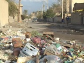 Stock Video Footage of Cars and Iraqi pedestrians make their way past trash accumulating on war-torn