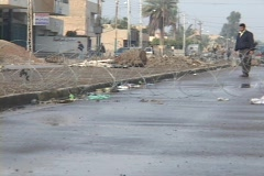 An Iraqi man stands guard at a crude roadblock on a war-torn Baghdad street. - stock footage