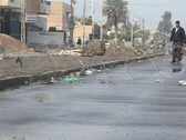 Stock Video Footage of An Iraqi man stands guard at a crude roadblock on a war-torn Baghdad street.