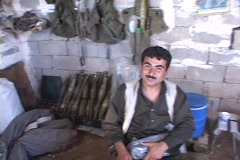A weapons dealer in Northern Iraq proudly poses with his arsenal. Stock Footage