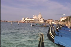 Moored gondolas bob up and down in the choppy waters of the Grand Canal in Stock Footage