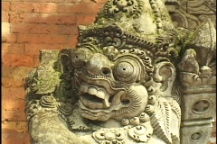 The grimacing face of a stone statue rests against a brick wall. Stock Footage
