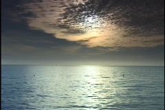 The sun shines through thin layers of clouds and shimmers across the ocean. Stock Footage