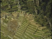 Stock Video Footage of The ruins of Machu Picchu rest against in a steep mountain hillside in Peru.