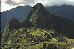 The ancient ruins of Machu Picchu lie in the mountain hillsides of Peru. - stock footage