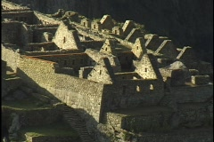 Stone walls and peaked rooftops line the hillsides at the ancient ruins of Machu Stock Footage