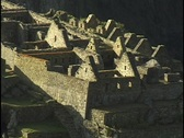 Stock Video Footage of Stone walls and peaked rooftops line the hillsides at the ancient ruins of Machu