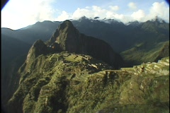 The ancient ruins of Machu Picchu nestle between the steep mountain ridges of Stock Footage