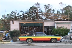Medium shot of a rainbow colored car in front of a destroyed house. Stock Footage