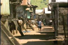 A villager walks between huts in Sulawesi, Indonesia. Stock Footage