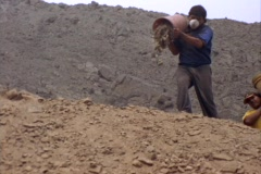 Medium-shot of two men dumping buckets of dirt at an archeological site. Stock Footage