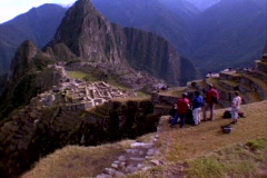 Wide-shot of tourists looking at Inca ruins of Machu Picchu in Peru. Stock Footage