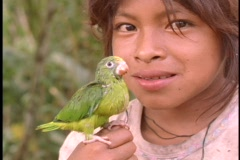 Close-up of a young girl holding a baby parrot in the Amazon rainforest. Stock Footage
