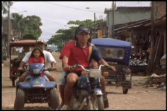 Medium-shot of local people driving a variety of small vehicles on their village Stock Footage