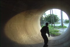 A skateboarder rides inside of a drainage tunnel. Stock Footage