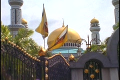 Flags wave in the breeze in front of the Gold palace of Sultan of Brunei in Stock Footage