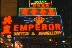 Buses drive beneath the Emperor Watch and Jewelry store neon-sign in Hong Kong. Stock Footage