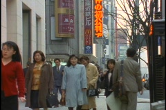 Crowds of pedestrians walk down a street in the Ginza District of Tokyo, Japan. Stock Footage