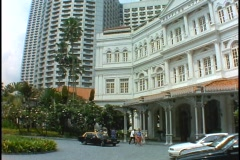 The skyline of Singapore rises above the Raffles Hotel in Singapore. Stock Footage