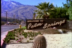 Traffic drives past the town sign for Palm Springs, California. Stock Footage
