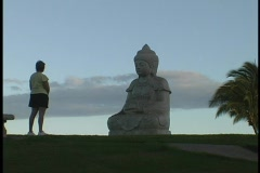 A tourist stands in front of a Buddha statue. Stock Footage