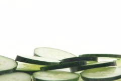 Slices of cucumbers fall into a pile.. Stock Footage