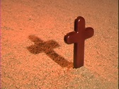 A shadow rises behind a Christian cross. Stock Footage