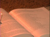 A gold cross rests on a Bible over the book of John. Stock Footage