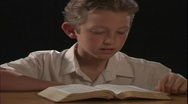 A young boy reads the Bible. Stock Footage