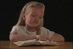 A young girl reads the Bible. Stock Footage