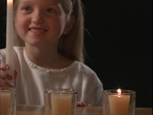 A young girl watches a flame of a candle. Stock Footage