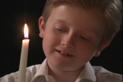 A young boy watches the flame on a candle. Stock Footage