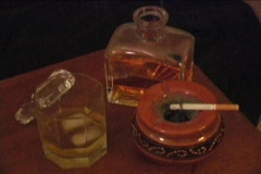 A cigarette burns in an ashtray with ice melting in a glass next to a bar bottle Stock Footage