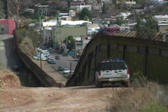 A police car watches the traffic on a busy street from a hill above. Stock Footage