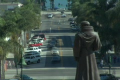 Traffic moves quickly on the streets adjacent to a statue of Junipero Serra. Stock Footage