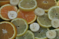 Water drips on slices of lemons, oranges, and bananas. Stock Footage