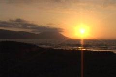 The sun sets near an ocean. Stock Footage