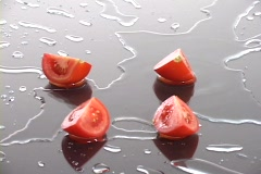 Fresh tomato wedges rest on a wet surface. Stock Footage