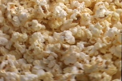 Buttered popcorn is shined on by spotlights in a display. Stock Footage
