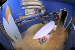 A fish-eye view of a man in a blue room building surfboards. Stock Footage