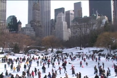 New Yorkers ice skate on a frozen lake in Central Park. Stock Footage
