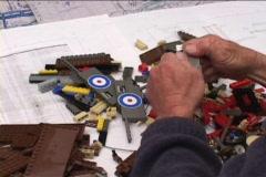 An artist assembles a Lego biplane. Stock Footage
