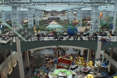 A large shopping mall includes amusement rides and a play area for children. Stock Footage
