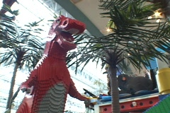 A giant dinosaur is part of a Lego display and play area for kids in the Mall of Stock Footage